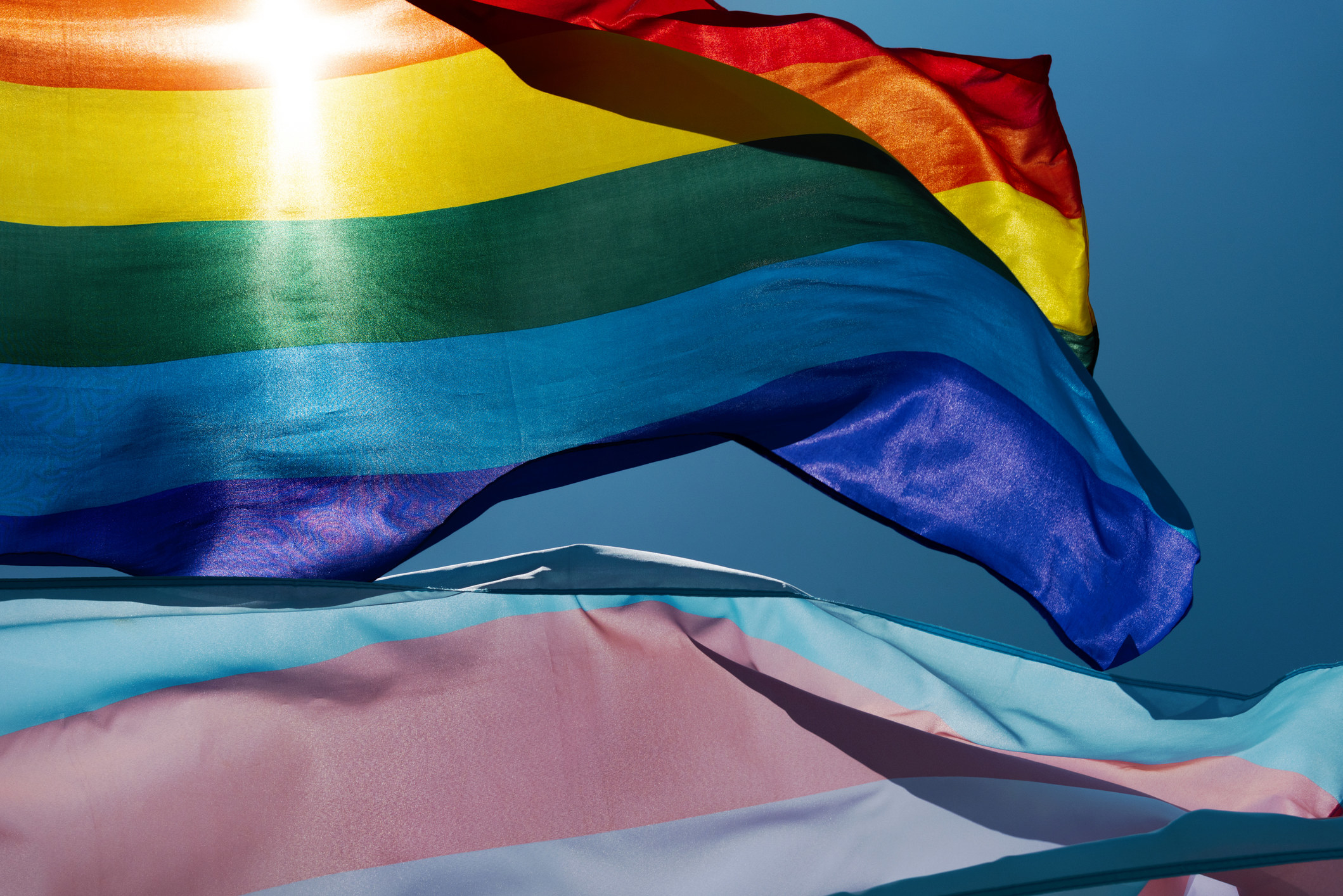 The Rainbow flag and the Transgender Pride flag fly high as the sun peaks through