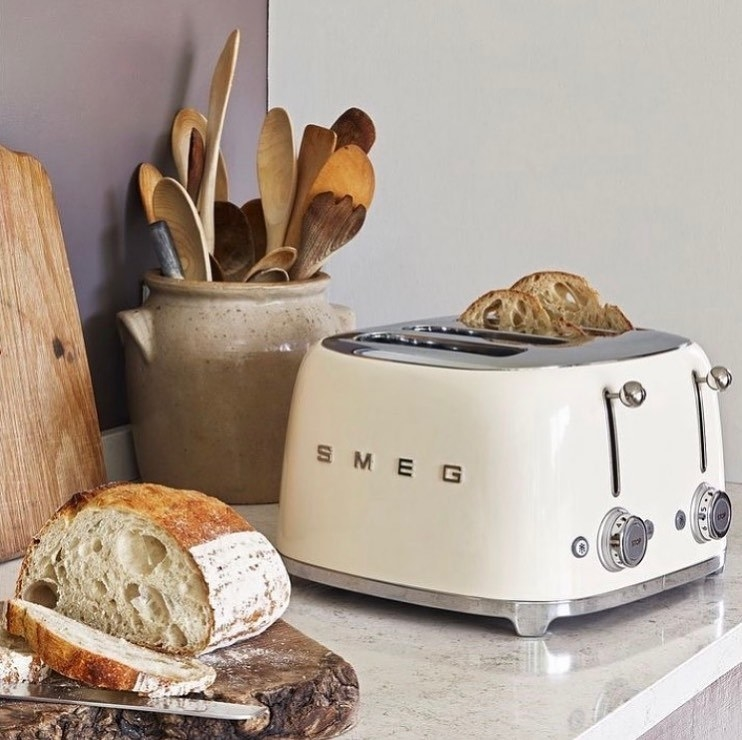 a white smeg toaster with freshly cut bread in it and next to it