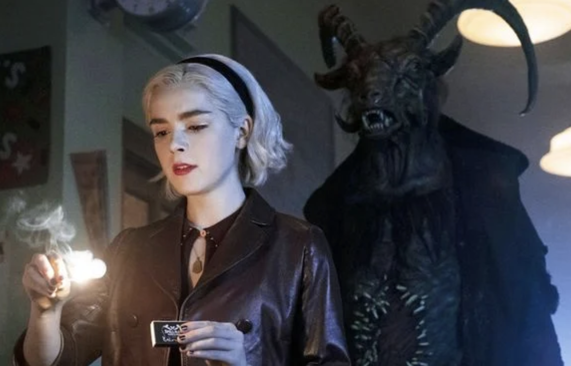 the devil stands behind Sabrina as she lights a match