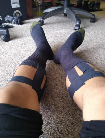 Reviewer wears black athletic tape around their calves before a workout