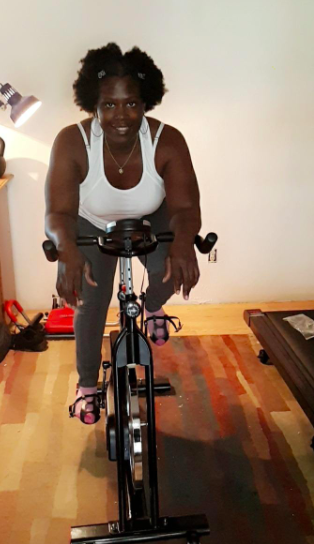 Reviewer sits on black and red stationary bike in their living room