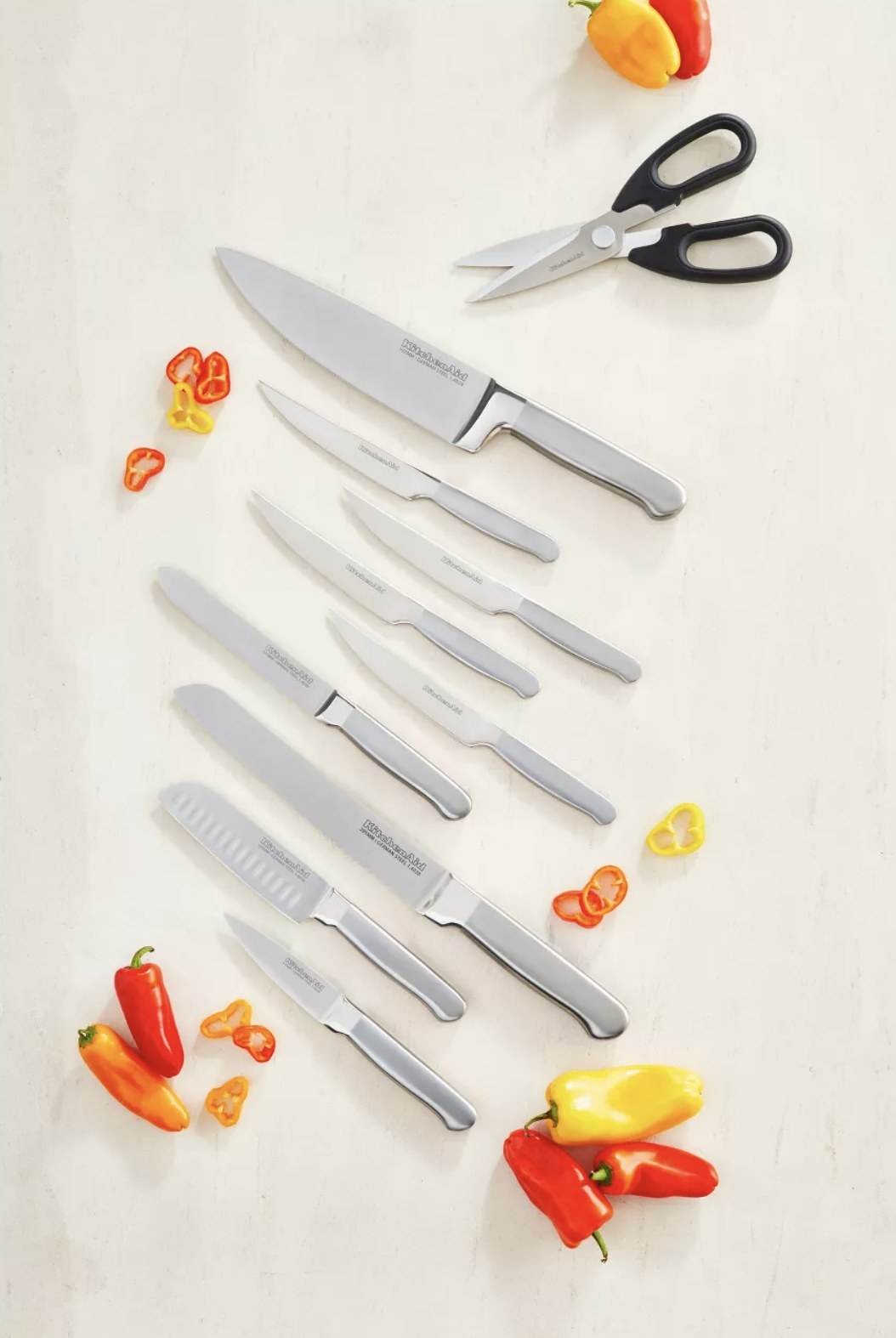 Ten pieces of metallic cutlery including knives and a pair of scissors