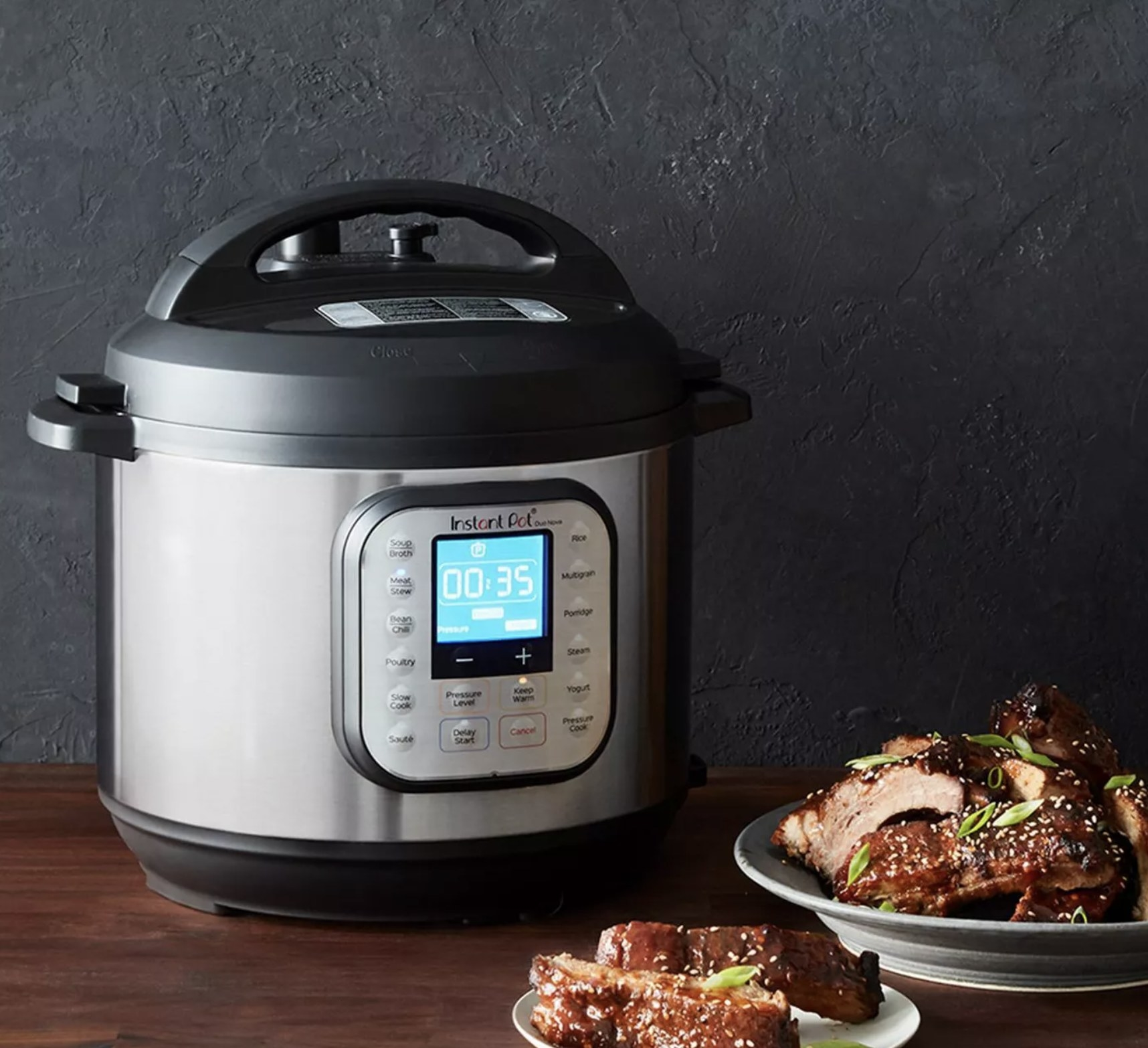 A silver pressure cooker pot with a black top and bottom and a digital screen not he front