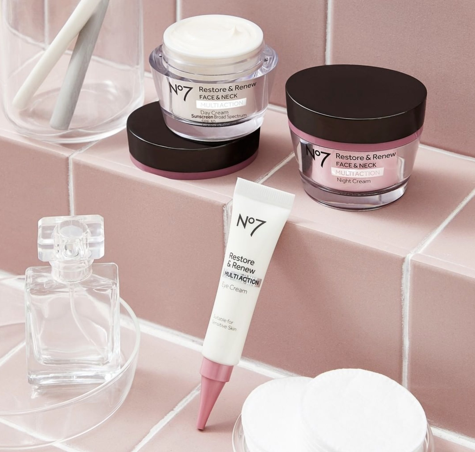 Skincare products in jars and tubes in a bathroom setting