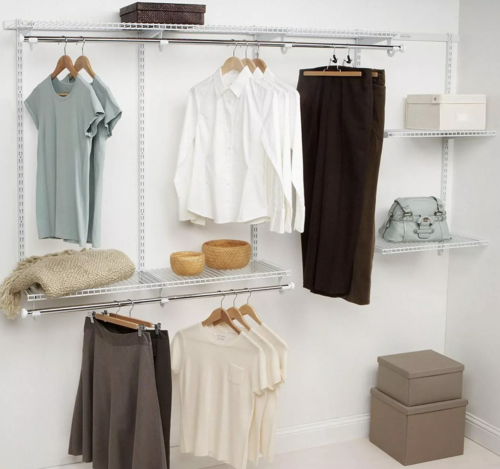 A white and silver metal closet system holding various items of clothing on hangers and shelves