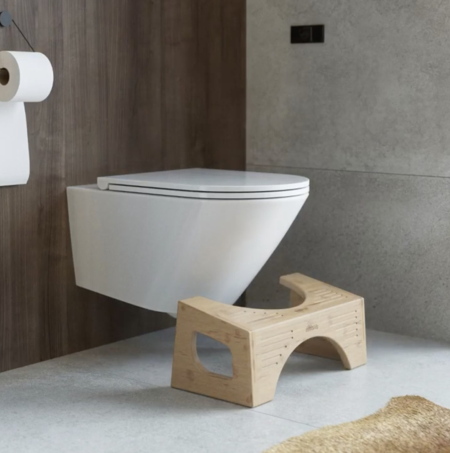 A bamboo wood-colored step stool positioned in front of a toilet