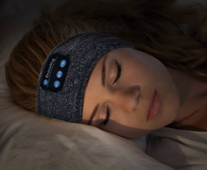 A model sleeping with the headphone band around her ears