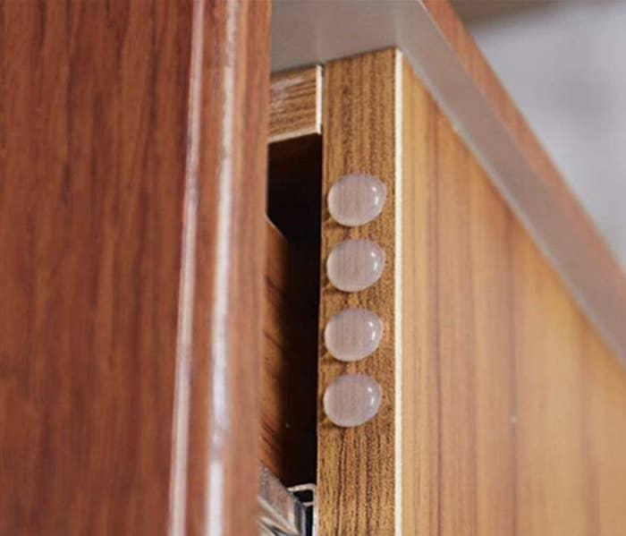 A set of four transparent penny-sized door bumper