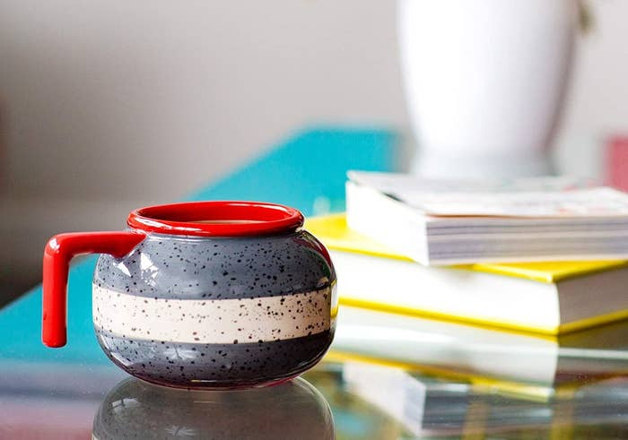 A mug in the shape of a curling rock on a side table
