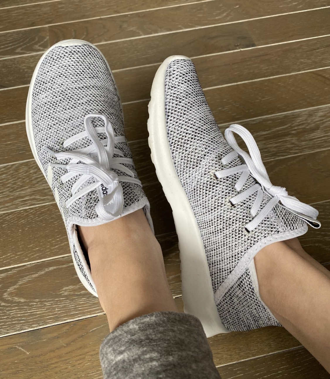 reviewer wearing grey and white sneakers with white laces