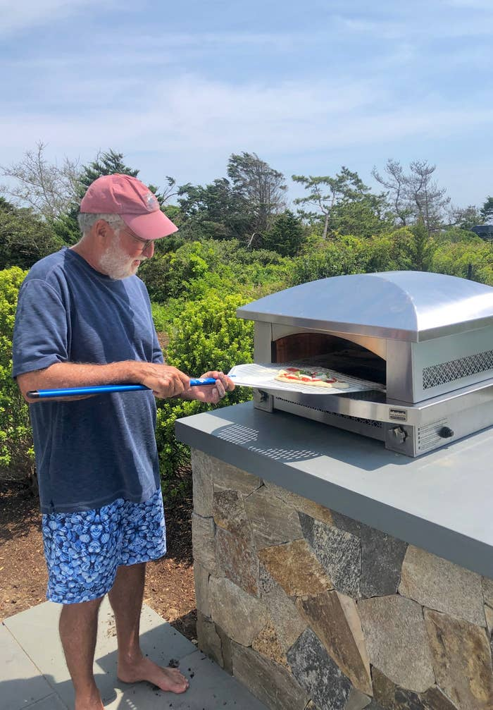 My father putting a pizza into his pizza oven.