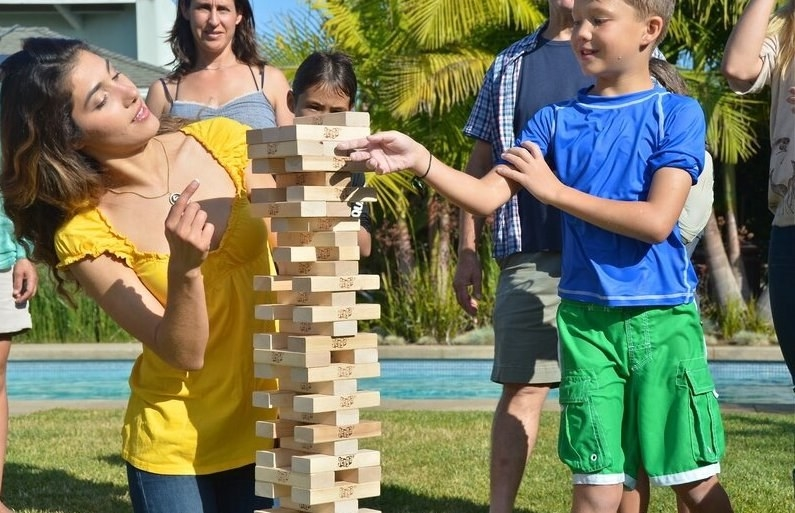 a group of adults and children playing the bigger version of Jenga outdoors