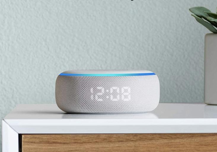 A white circular Amazon Echo on a bedside table