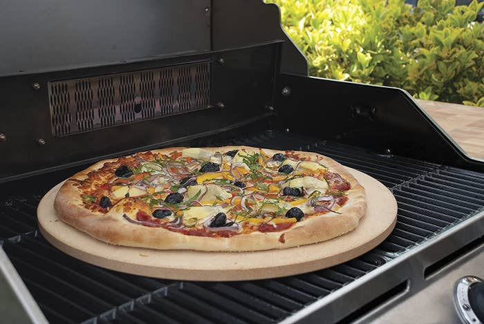 A homemade pizza on the Pizzacraft stone on an outdoor grill.
