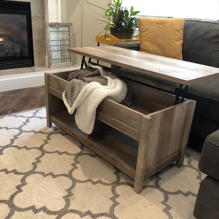 the coffee table in a light wood color opened to showcase the piece that opens for storage