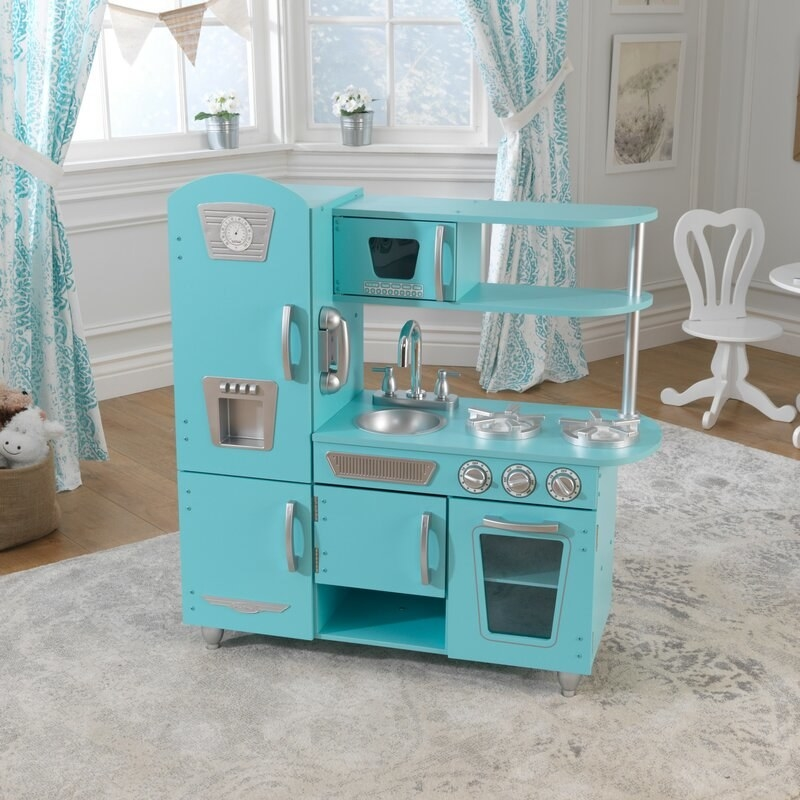 a mini retro-styled kitchen in turquoise blue with a fridge, freezer, stove, oven, sink, microwave, and shelving