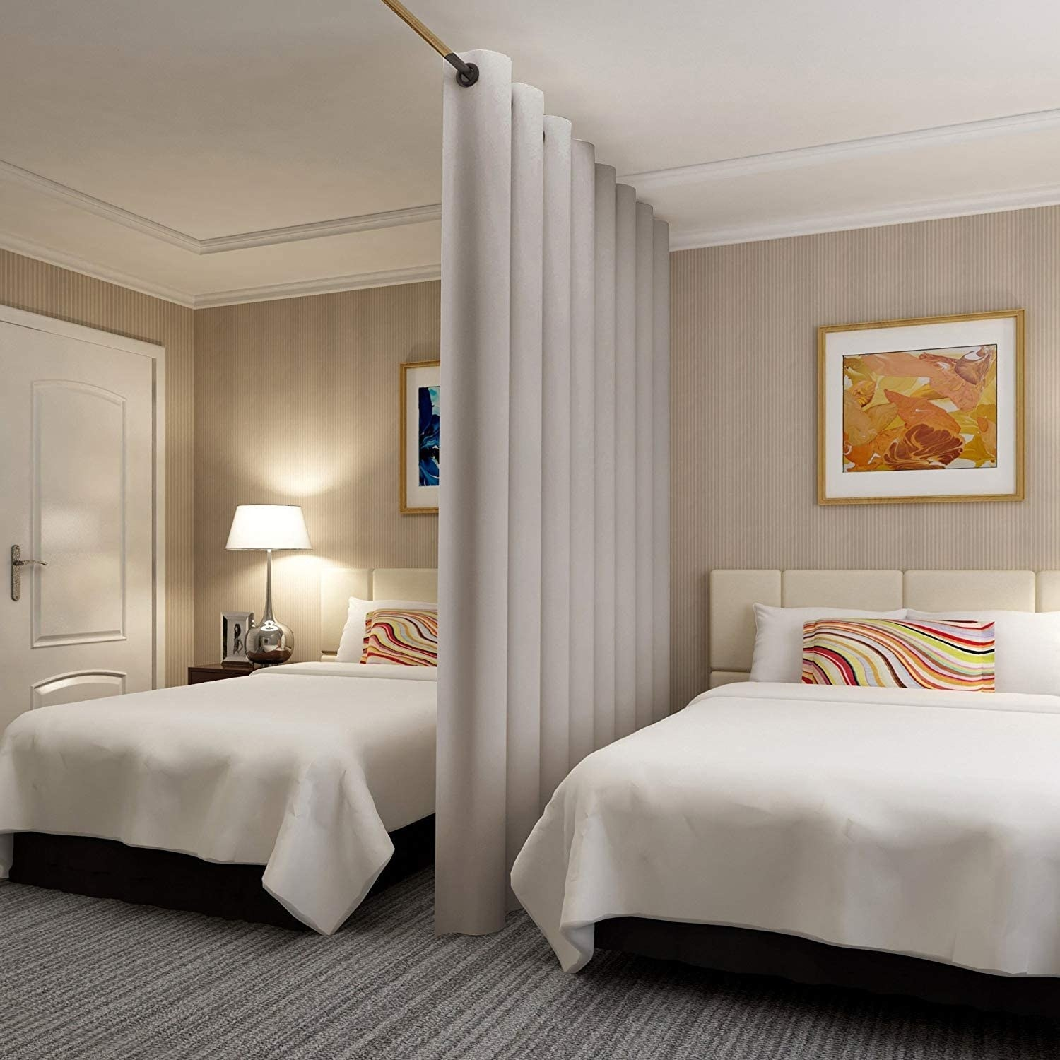 Two beds in a bedroom divided by a thick white hanging curtain on a rod