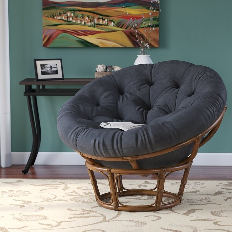 a thick, black microfiber circular cushion inside a circular wicker platform