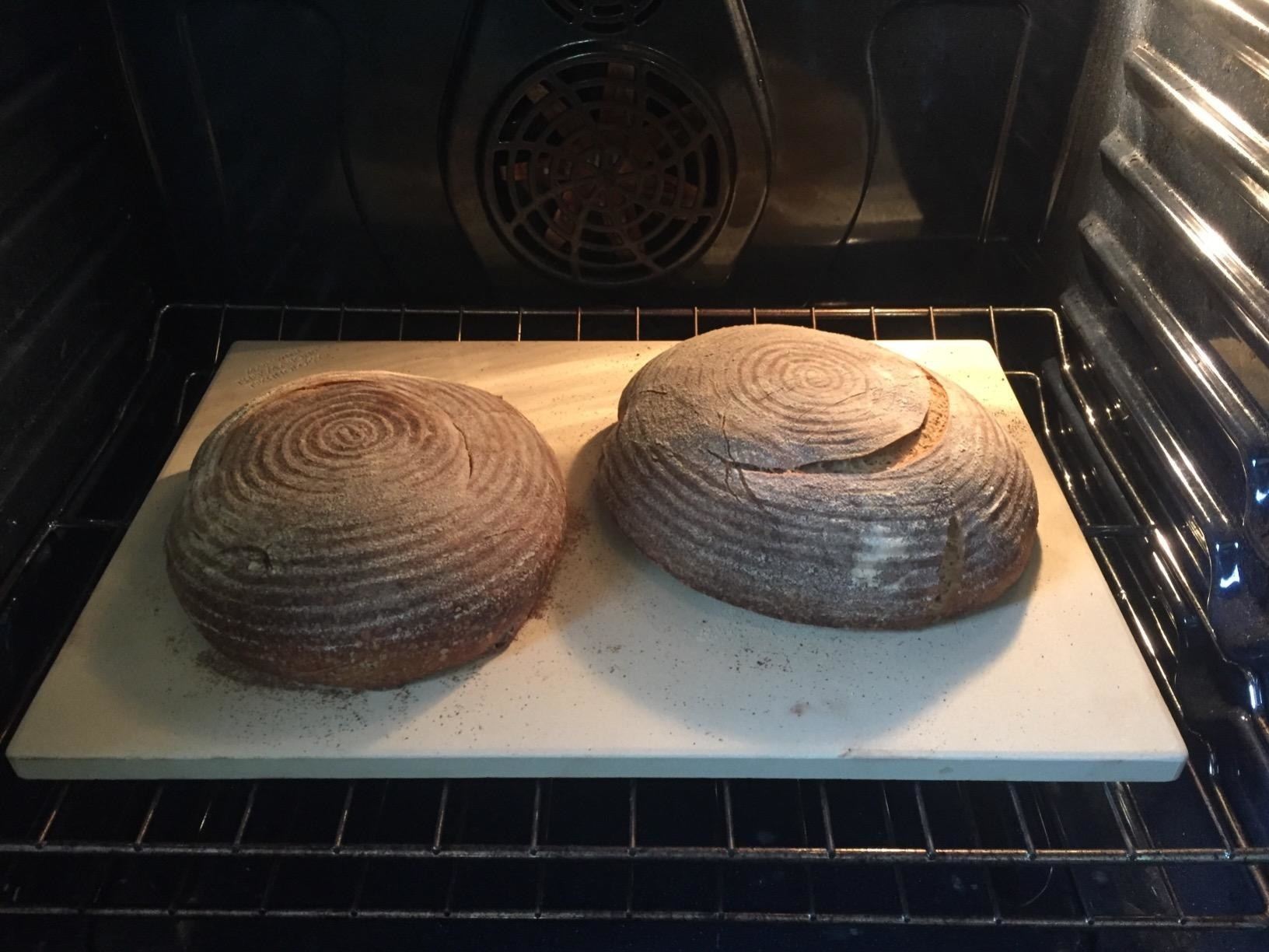 Two loaves of bread cooking on a pizza stone.