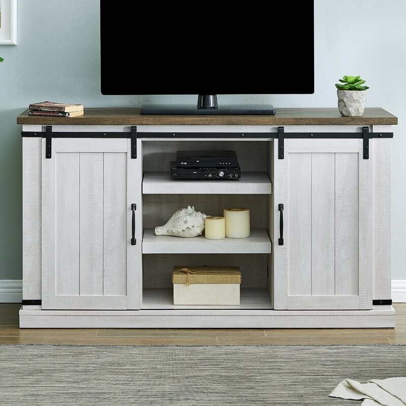 the nearly-white wooden tv stand with a darker wood top, two cabinets, three shelves, and black metal accents