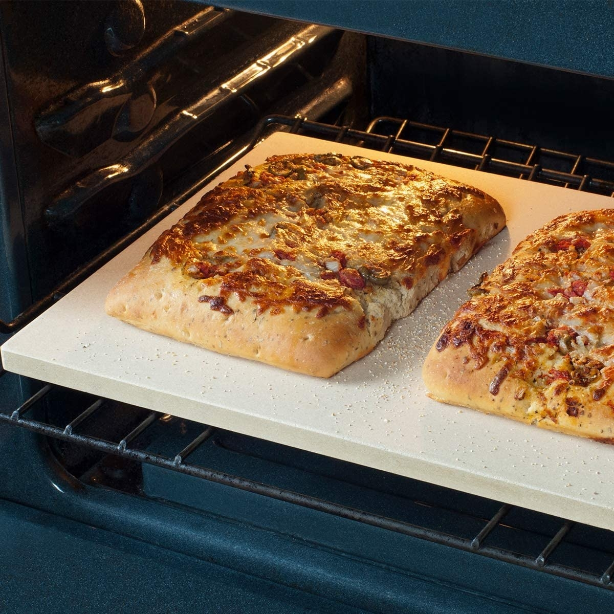 Two rectangular pizzas cooking on a pizza stone.