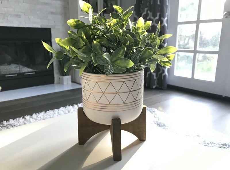 a leafy green faux plant in a white pot with golden geometric patterns on it sitting atop a dark brown wooden stand