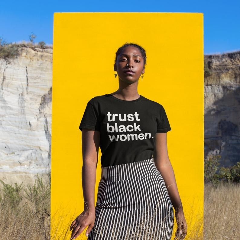 "person wearing black T-shirt that says ""trust black women"" in white text"