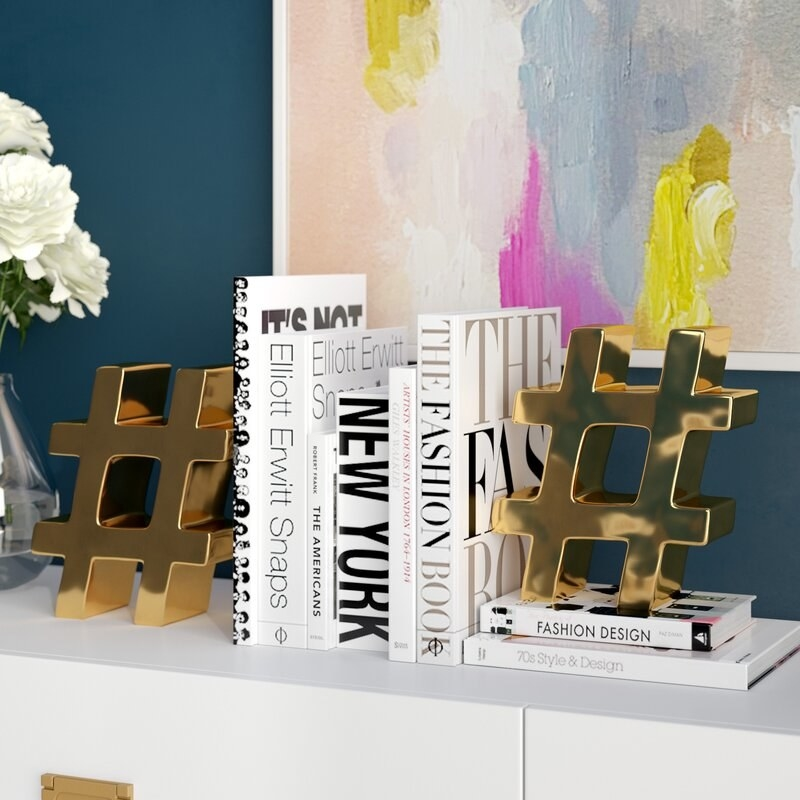 six black and white books in between two golden oversized hashtag symbol bookends