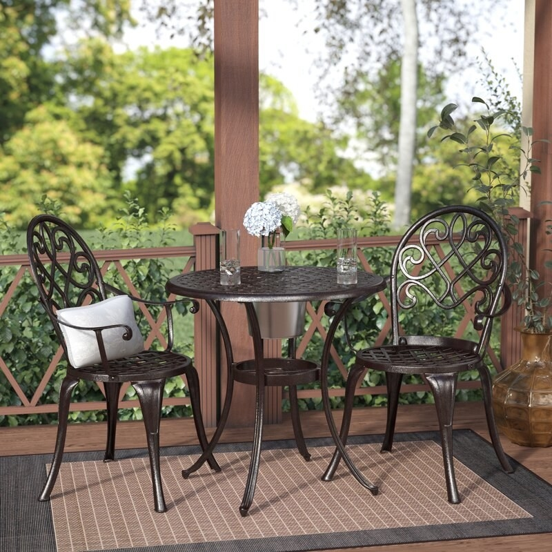 a cast aluminum bistro set with two pretty chairs with a curvy metal design on the back and a small table with a similar design on the table top