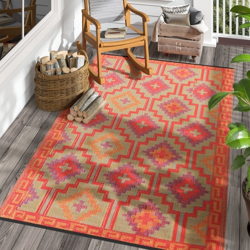 a contemporary rectangular rug with a pattern across it including orange, red, purple, and tan