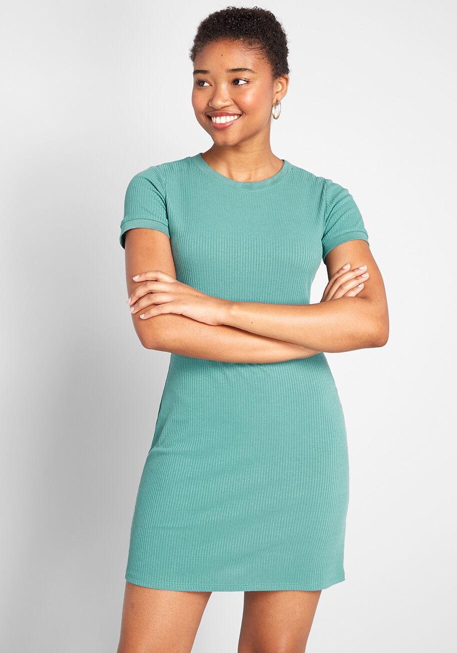 A model wearing the ribbed mini dress in seafoam green