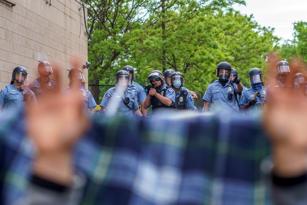 A police officer aiming a weapon at a protester who has their hands up
