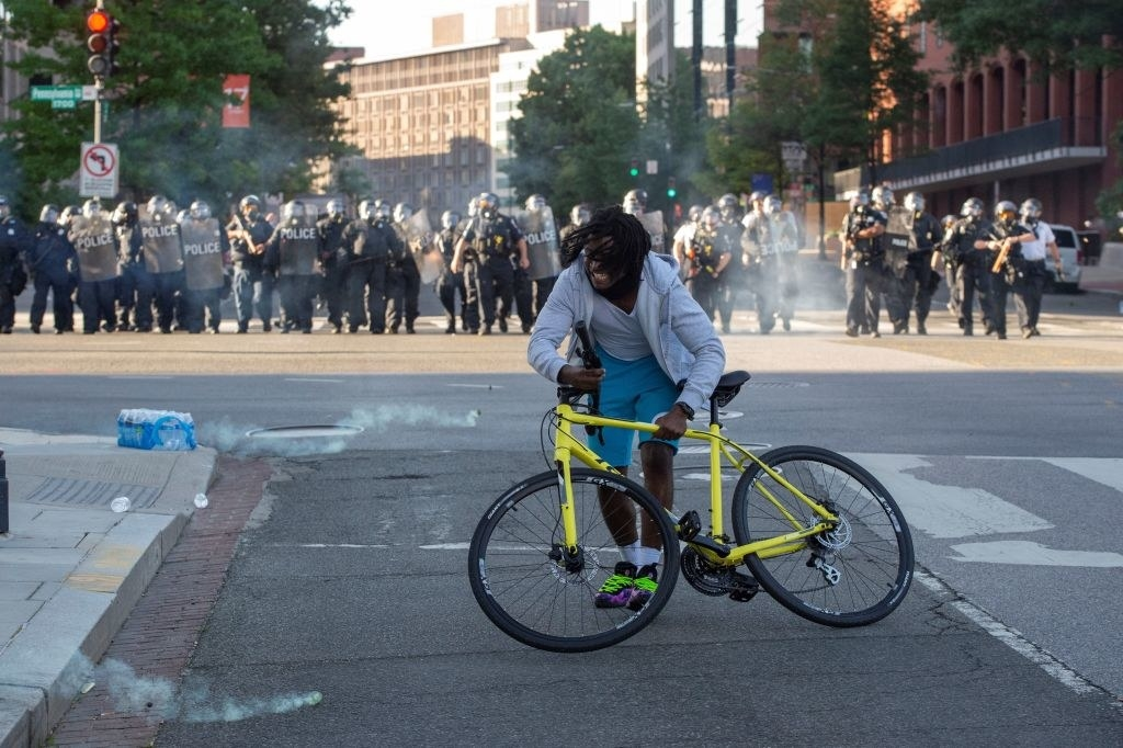 A BLM protestor trying to escape tear gas being deployed by a line of police officers