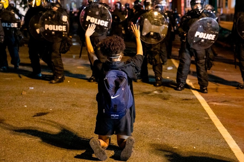 Police in riot gear face off against a Black Lives Matter protestor who is kneeling with their hands up