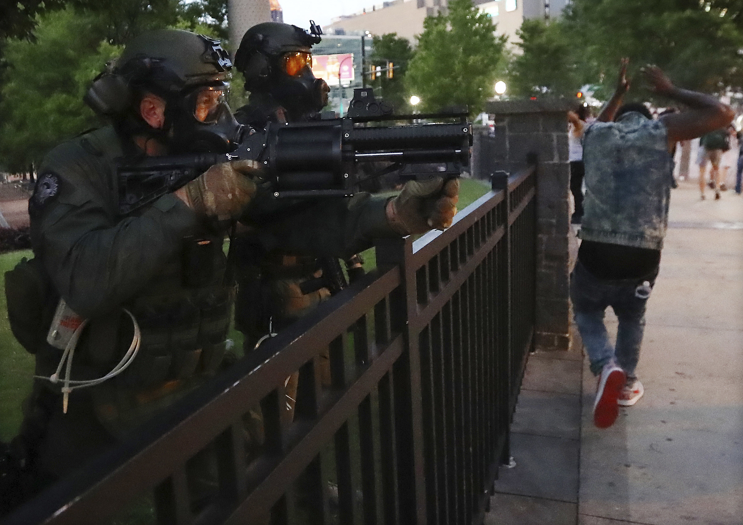 Police officers pointing weapons at BLM protestors