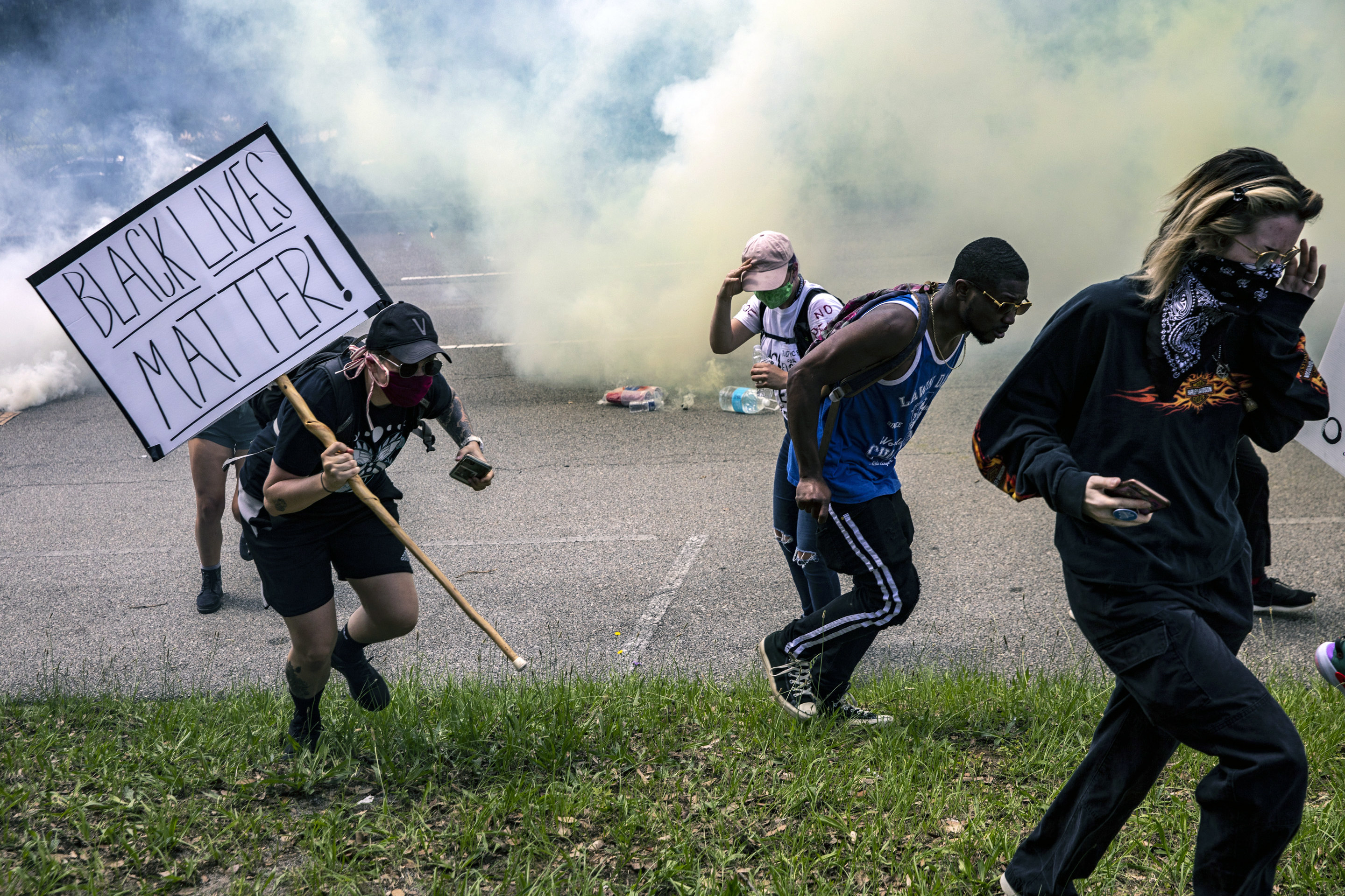 Protesters run from tear gas deployed by the police