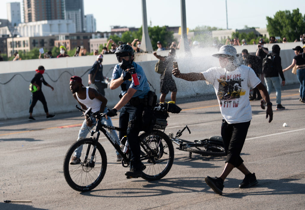 A police officer on a bicycle spraying a protester as he walks down a street