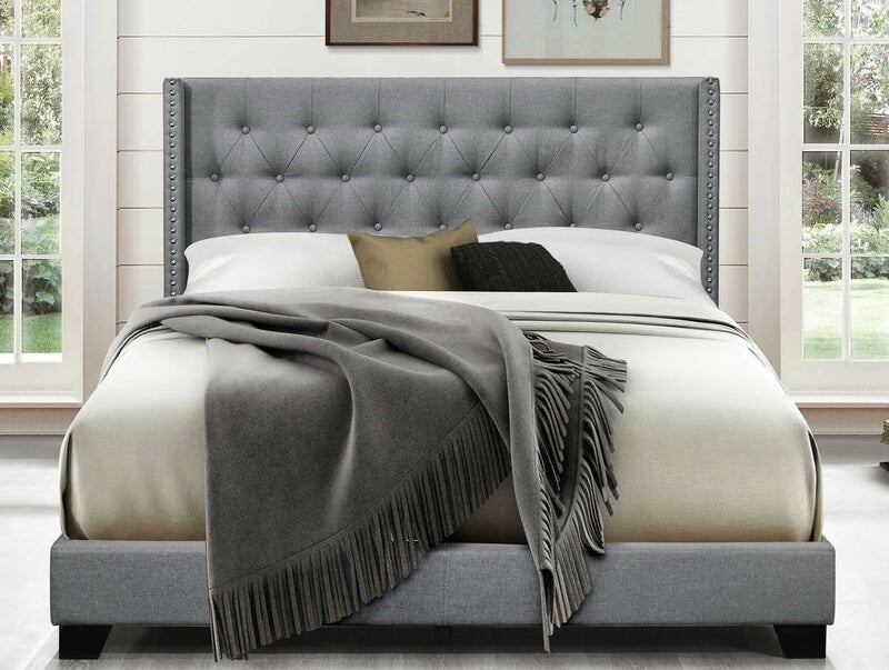 a bed with a grey tufted head, nail head trim and matching grey platform