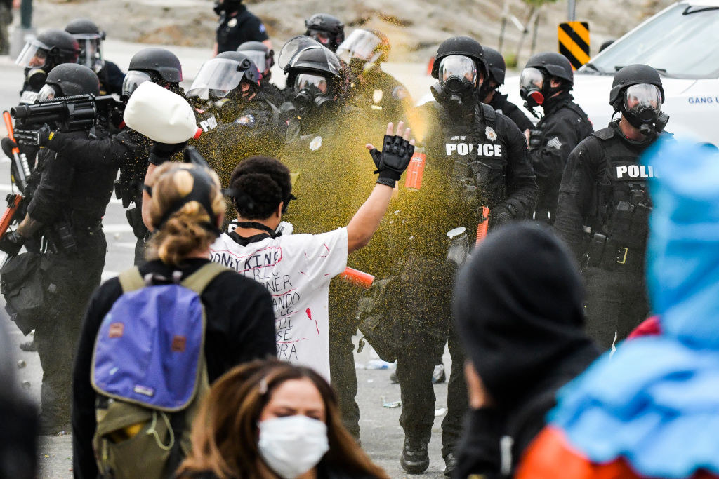 Officer in full riot gear pepper spraying a protester who has their hands up