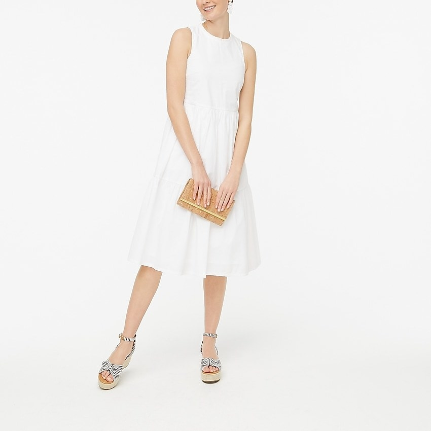 A white sleeveless dress that falls just below the knee