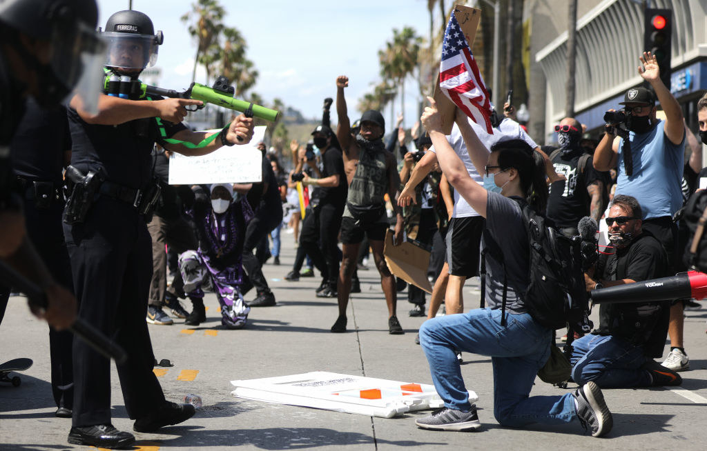 Police officer aiming a weapon at a protester who's taken a knee and held up a sign