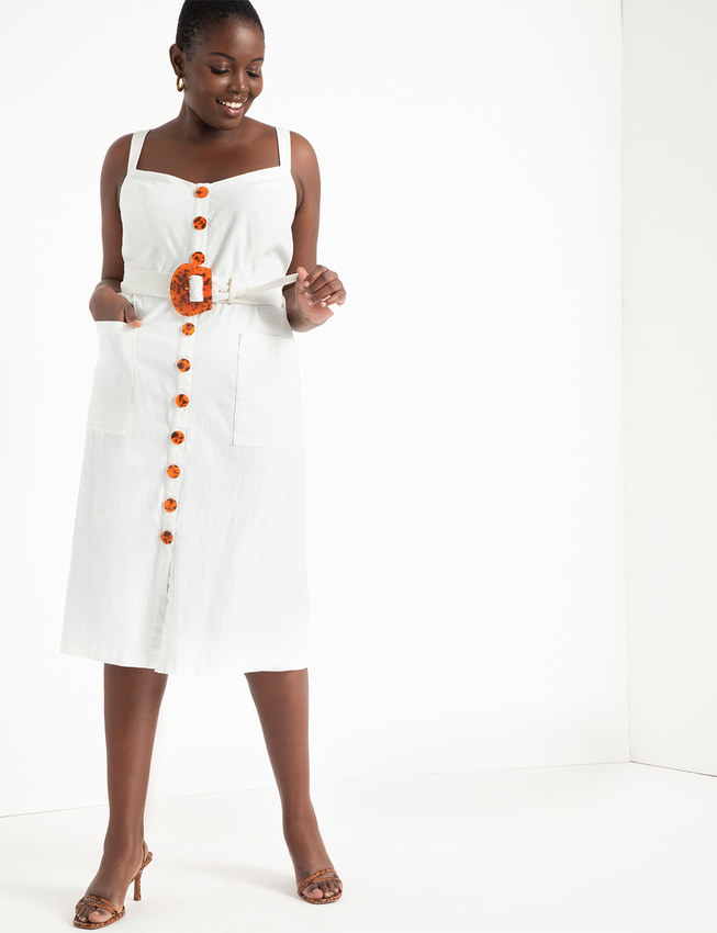 A model wearing the white, sleeveless dress and looking down at the tortoise shell buttons and belt