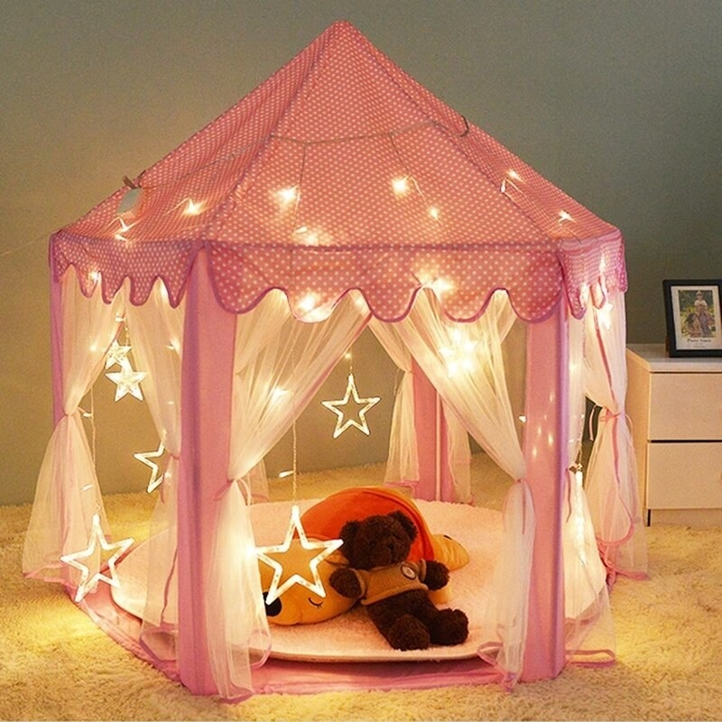 a circular tent with a pink polka-dotted roof, white flowy netting to keep bugs out (but can be tied away for indoor use) and twinkling star-shaped LED lights throughout