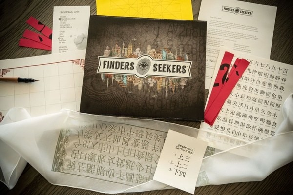 The Finders Seekers box cover surrounded by deciphering tools