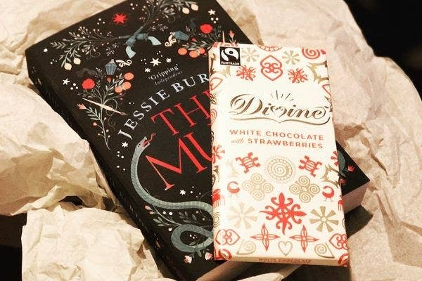 A book and a bar of white chocolate with strawberries