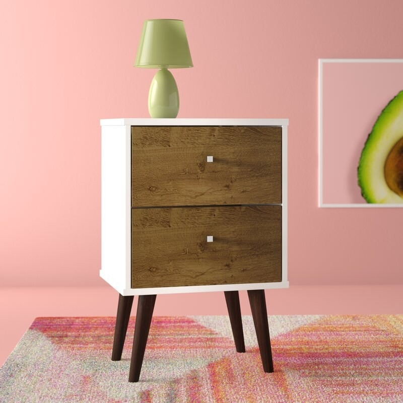 the night table with brown drawers, a white exterior, dark brown legs, and tiny white squares as the knobs