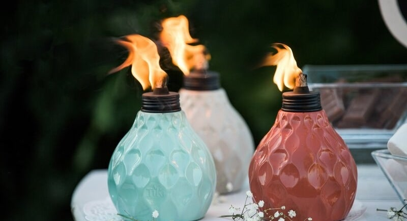 rounded tabletop tiki torches with an intricate seashell-like design on them, one is red, one is light blue, one is white