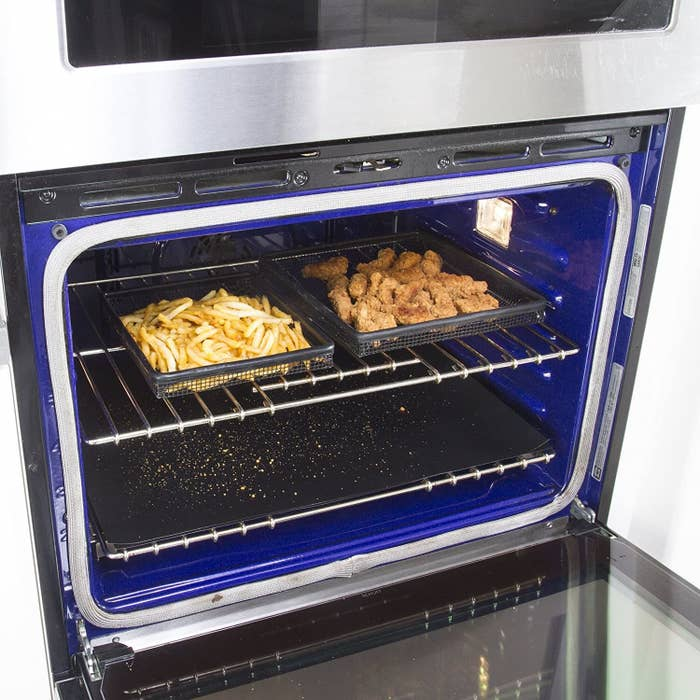 An oven with a liner sheet on the bottom catching crumbs