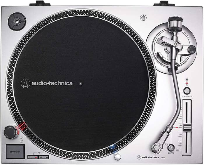 A silver turntable with a black platter mat