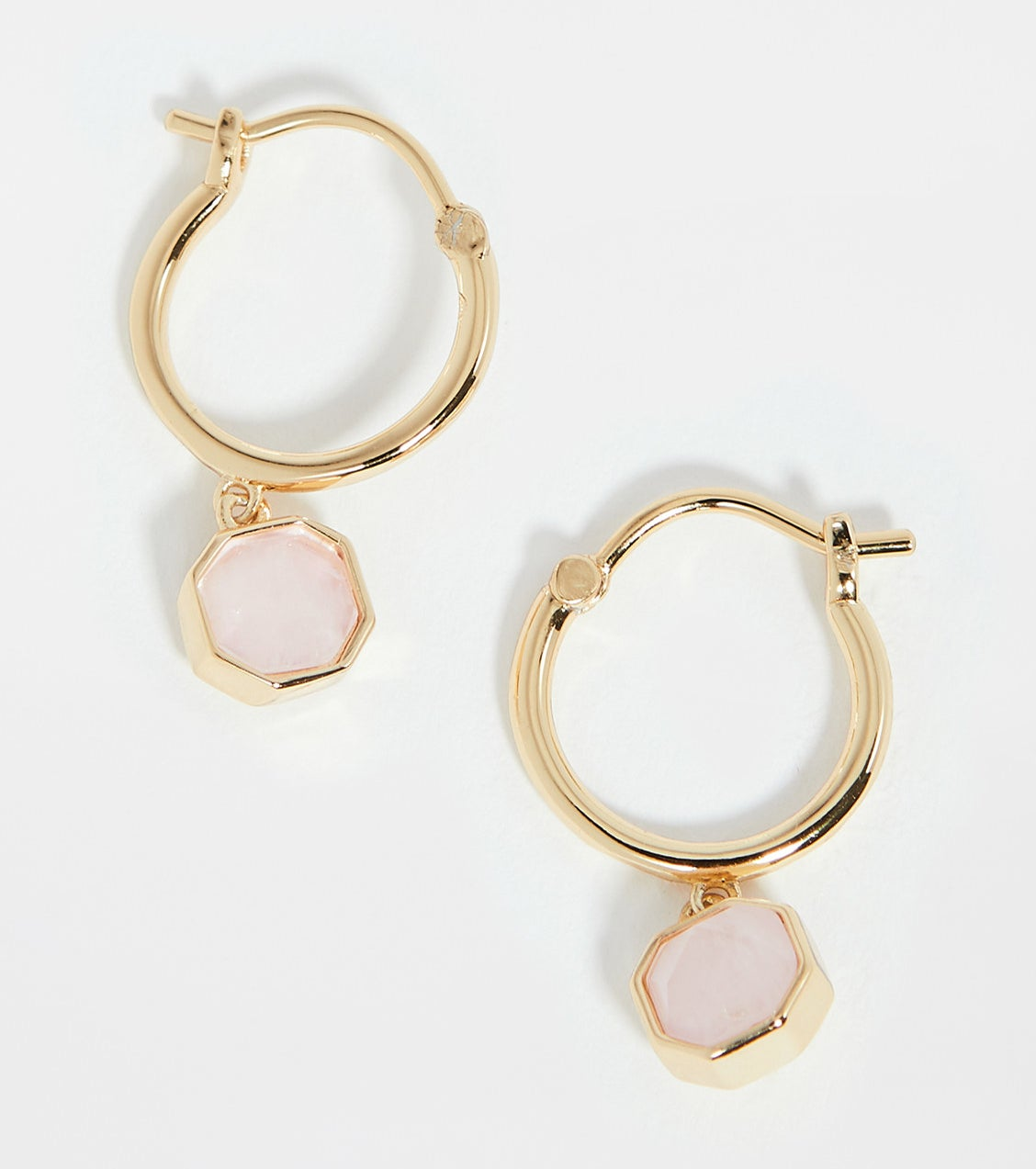 hold hoop huggie earrings with rose quartz stones hanging from he hoops, encircled with gold